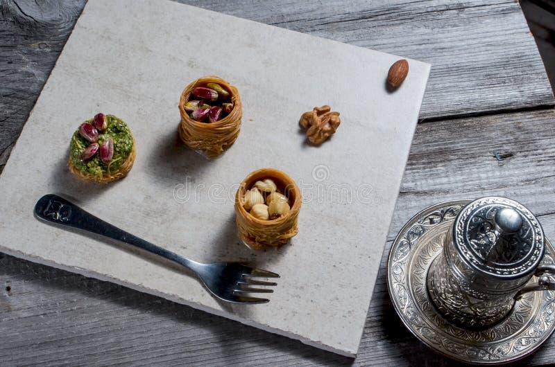 与在轻的背景和传统铜服务的土耳其咖啡设置的欢欣 被分类的传统土耳其dilight或lokum 免版税库存图片