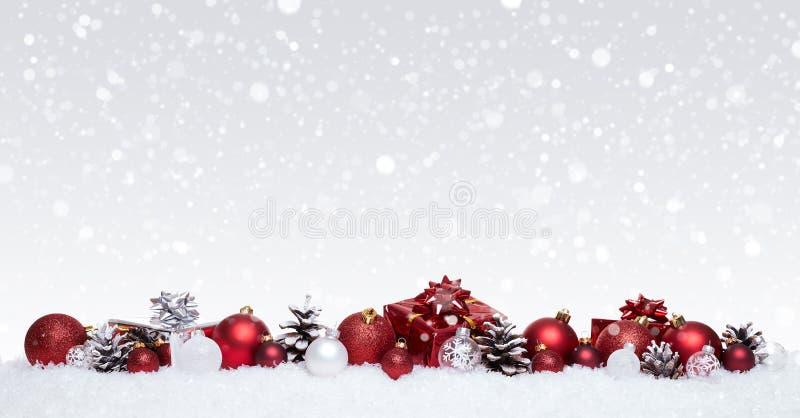 与在雪连续隔绝的xmas礼物的白色和红色圣诞节球 免版税库存图片