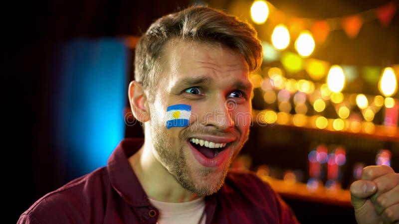 与在面颊愉快的队赢得的竞争绘的阿根廷旗子的足球迷 免版税库存照片