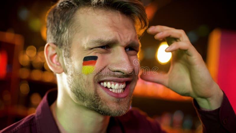 与在面颊挥动的手绘的德国旗子的失望公爱好者,失败上 图库摄影
