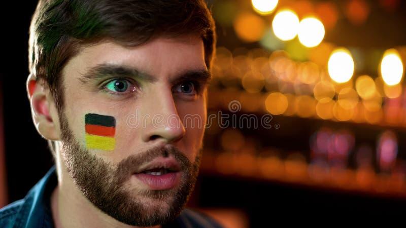 与在面颊看着电视绘的德国旗子的不快乐的男性,队丢失的比赛 库存图片