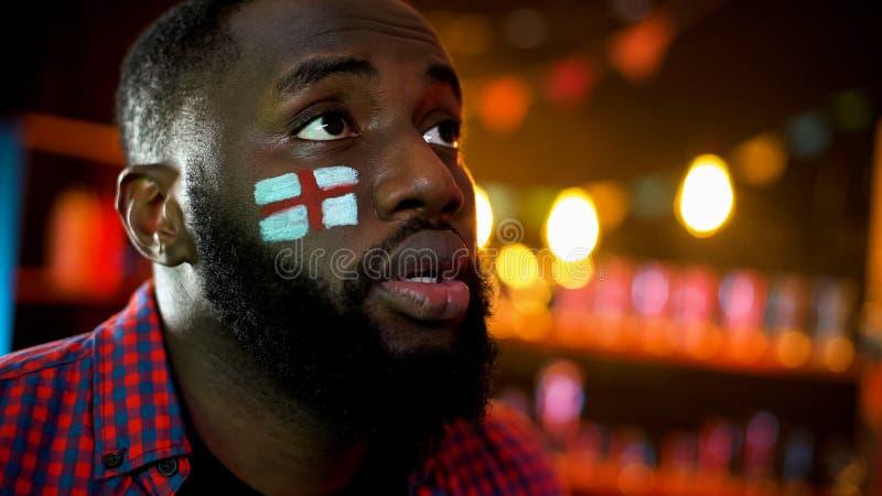 与在面颊等待的胜利绘的英国旗子的黑足球迷,希望 免版税图库摄影