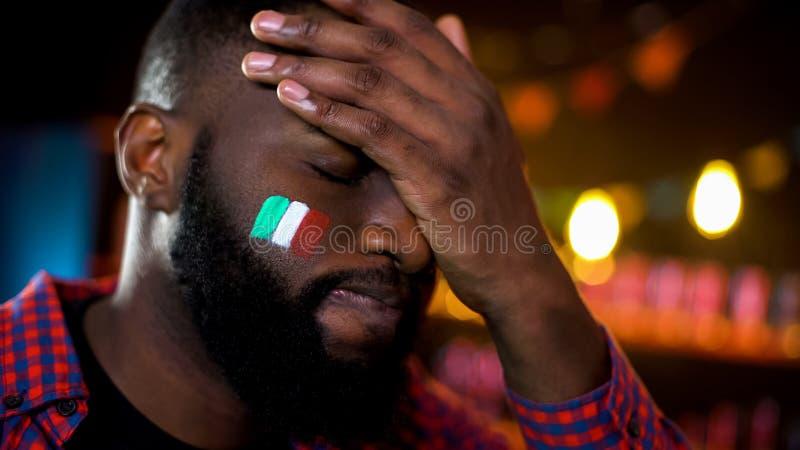 与在面颊绘的意大利旗子的急切黑足球迷取得facepalm损失 图库摄影
