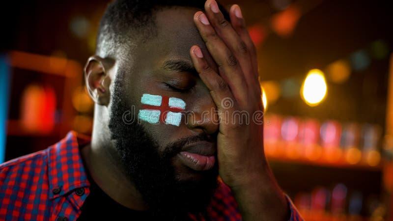 与在面颊绘的英国旗子的黑男性辜负了足球队失败 免版税库存图片