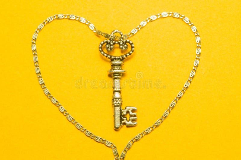 与在黄色背景隔绝的银色链子的葡萄酒钥匙 库存照片