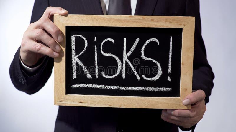 与在黑板写的惊叹号的风险,拿着标志的企业人 免版税库存照片