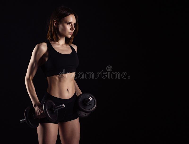 与在黑背景隔绝的哑铃的运动的肌肉女性做的锻炼 运动少妇做与w的健身锻炼 免版税库存图片