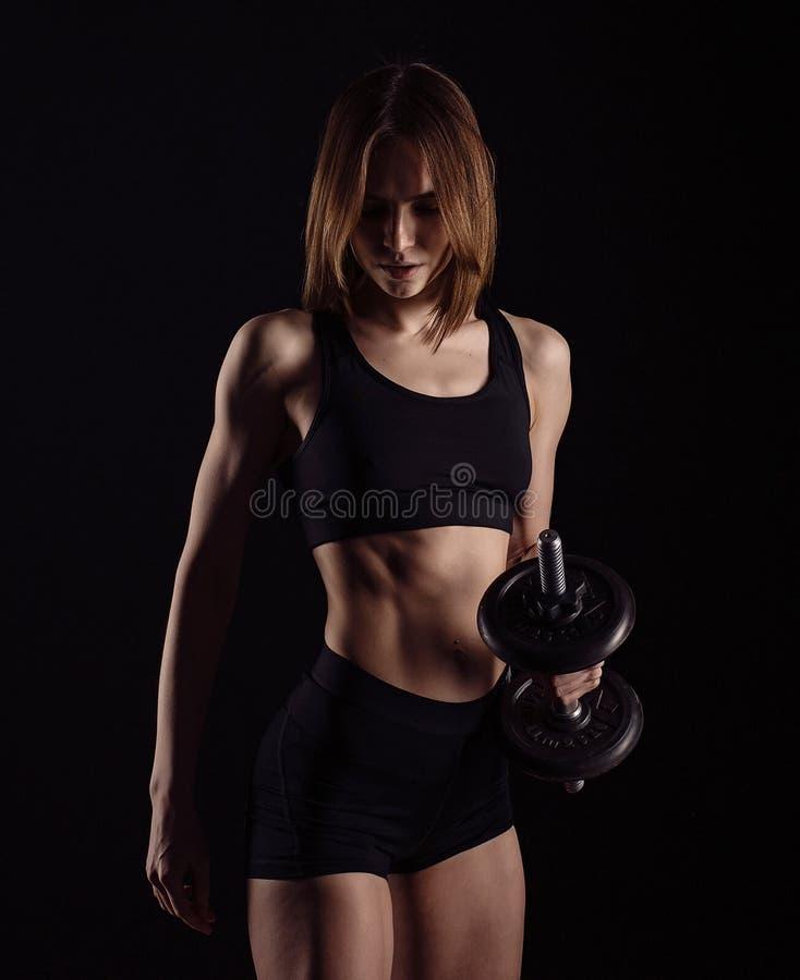 与在黑背景隔绝的哑铃的运动的肌肉女性做的锻炼 运动少妇做与w的健身锻炼 免版税图库摄影