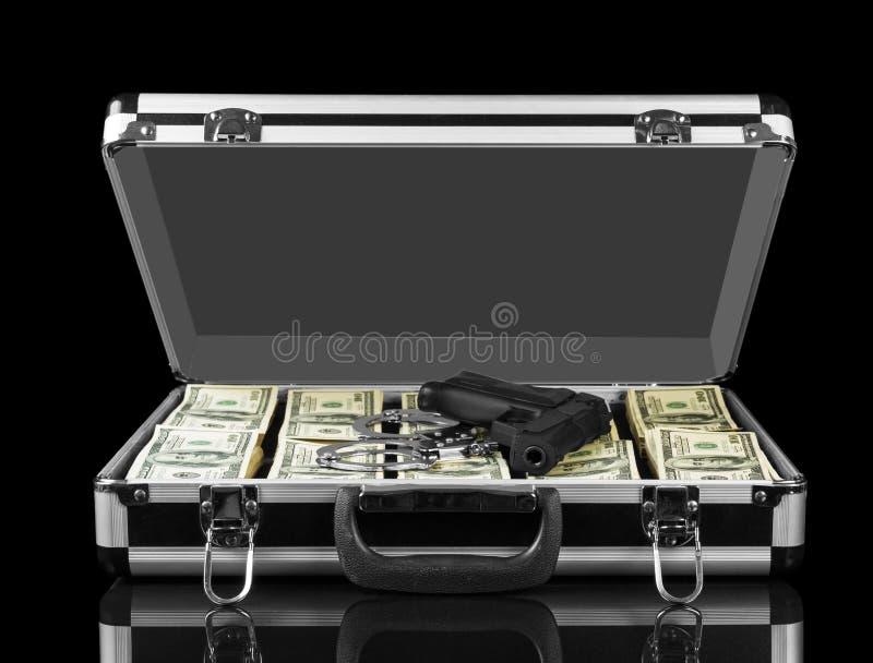 与在黑背景和手铐的被打开的案件隔绝的美元武器 库存图片