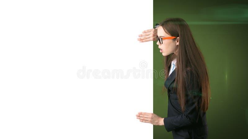 与在绿色被隔绝的空白的白板的惊奇的女商人画象 与长的头发的女性模型在玻璃 库存图片