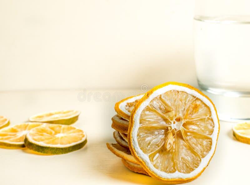 与在backgound的玻璃水一起被堆积的干柠檬切片 E 图库摄影