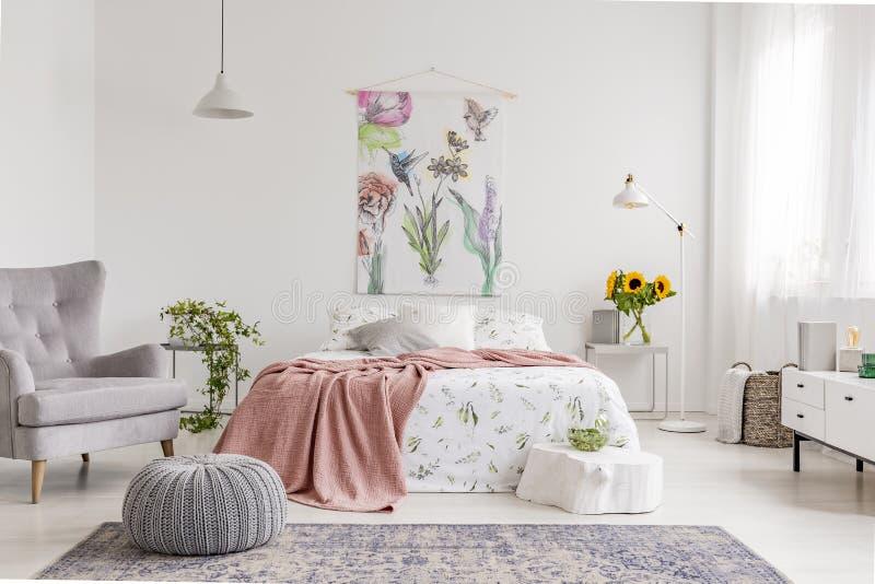 与在g穿戴的床上的一种织品和鸟绘的墙壁艺术的大自然爱好者` s明亮的卧室内部花 免版税库存照片