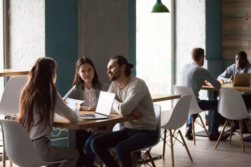 与地产商的千福年的夫妇购买房子会议在咖啡馆 免版税库存图片