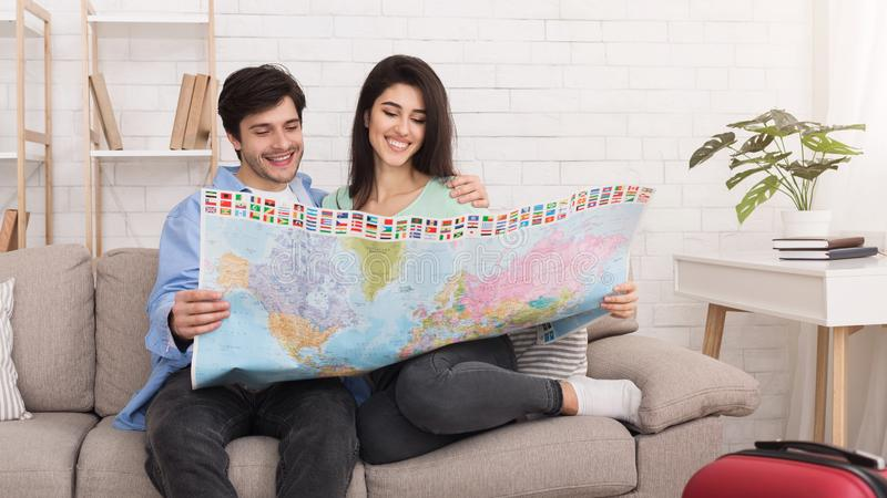 与地图的爱的夫妇计划的蜜月假期 免版税库存图片