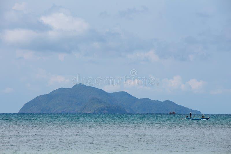 与地方渔夫小船的山在漂浮在有明亮的天空的海的右边在背景中下午 库存图片