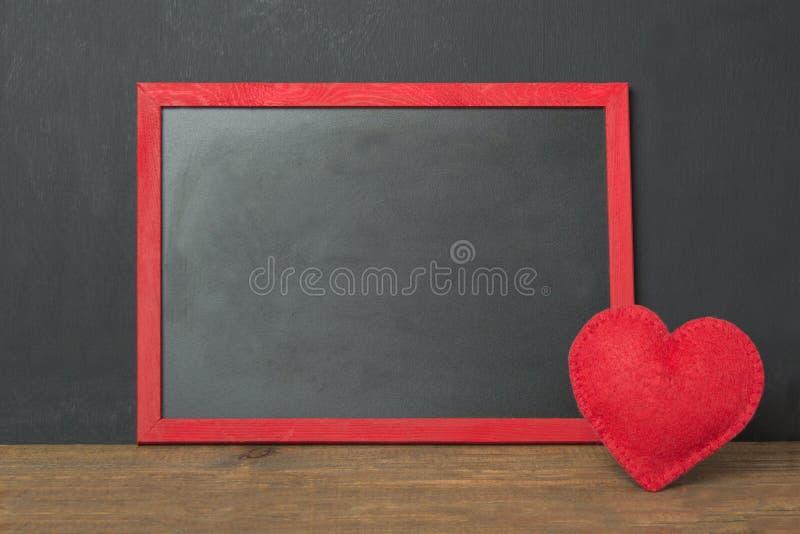 与地方的黑板框架您的文本和红色的感觉心脏作为在木桌上的装饰 看板卡s华伦泰 嘲笑 库存图片