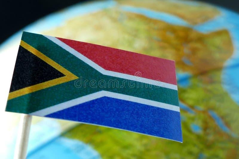 与地球地图的南非旗子作为背景 免版税库存图片