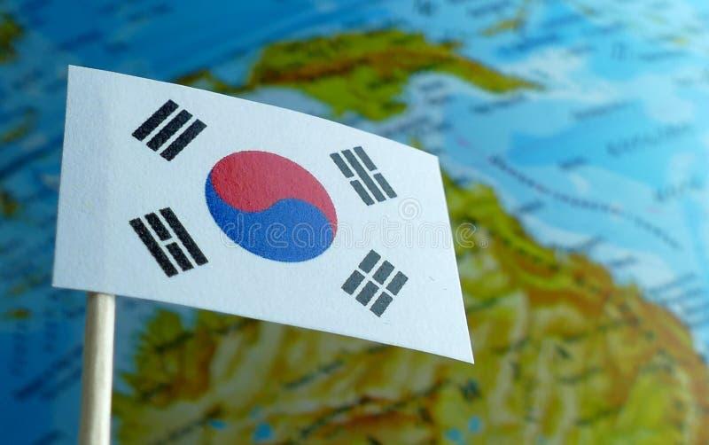 与地球地图的韩国旗子作为背景 免版税图库摄影