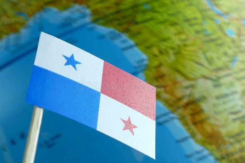 与地球地图的巴拿马旗子作为背景 免版税库存照片