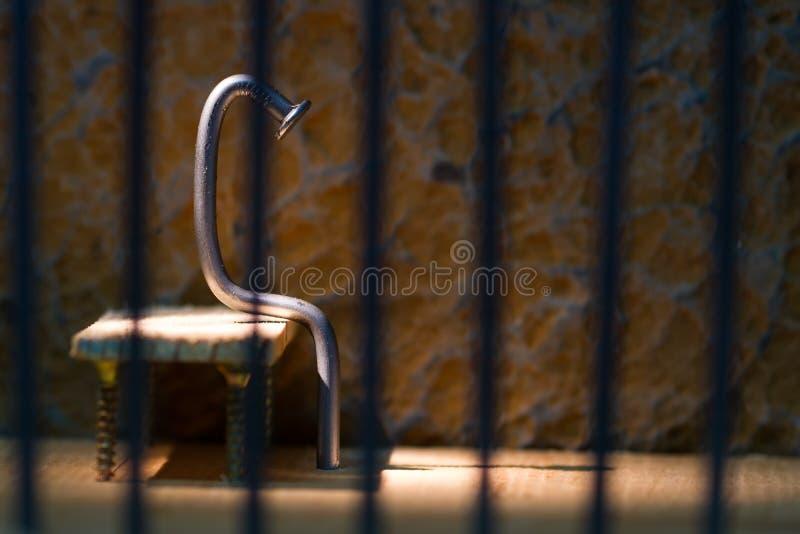 与坐关在监牢里的铁钉子的概念性监狱照片 库存图片
