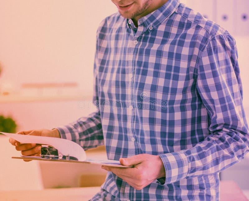 与坐在办公室的红色文件夹的微笑的商人 免版税库存图片