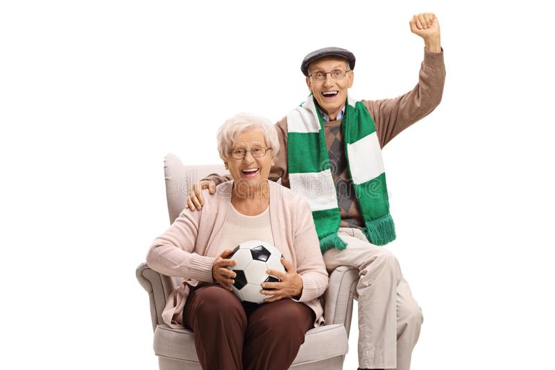 与坐在扶手椅子的橄榄球和围巾的快乐的老人和女子足球迷 库存照片
