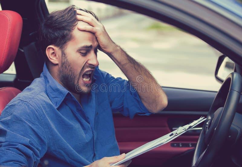 与坐在汽车里面的纸的被注重的绝望人司机 库存照片