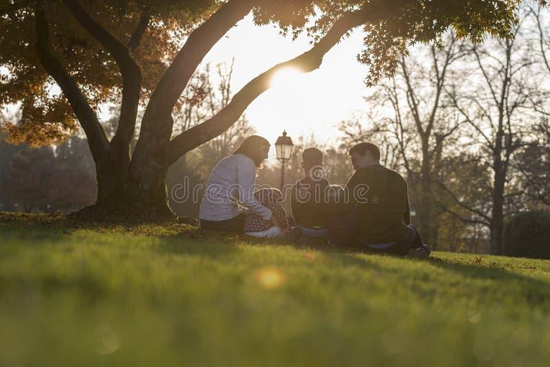 与坐在秋天树下的三个孩子的年轻家庭 库存照片
