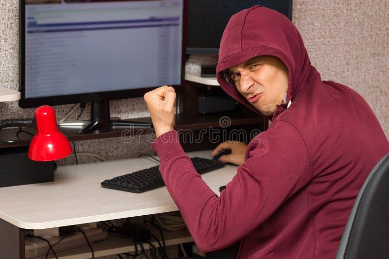 与坐在计算机的邪恶的面孔的互联网拖钓 非常坏人高兴写讨厌的事在论坛 免版税库存照片