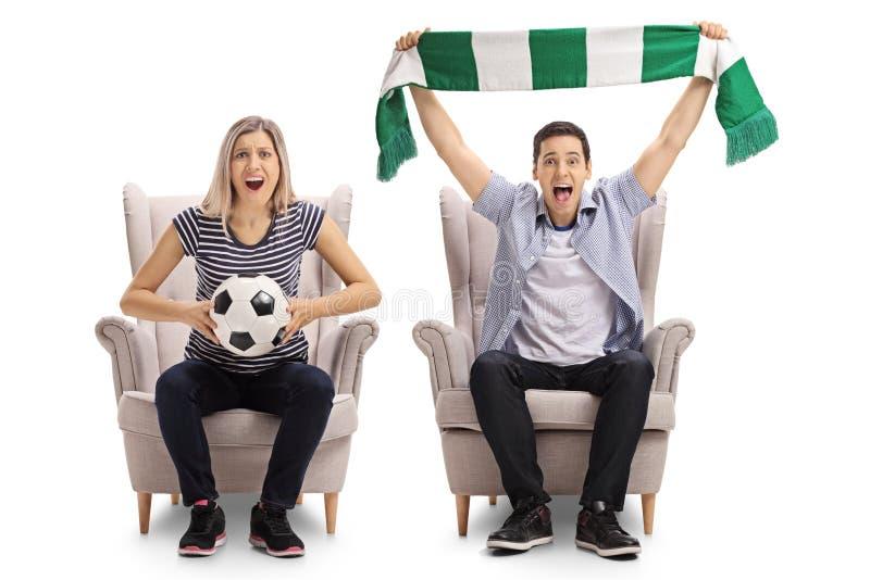 与坐在armch的橄榄球和围巾的激动的足球迷 库存照片