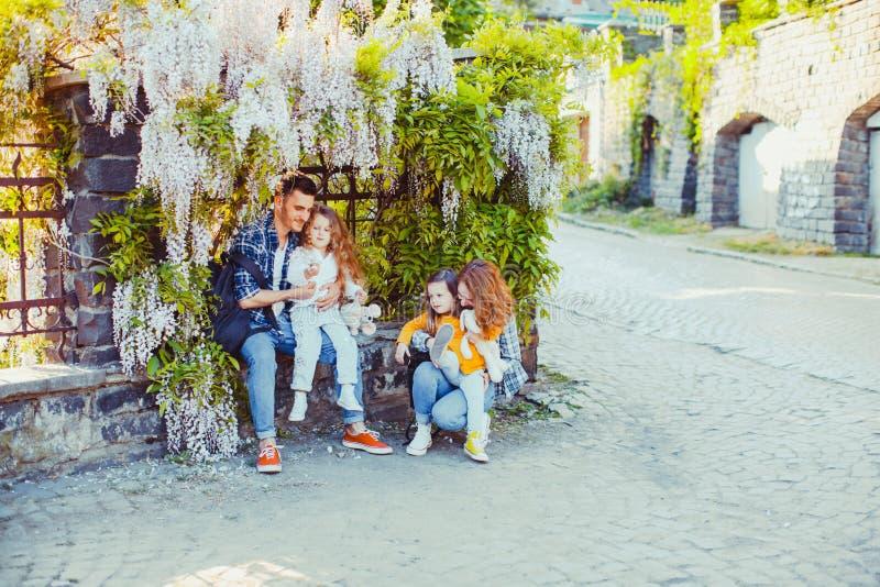 与坐年轻的家庭的紫藤花下 免版税库存照片