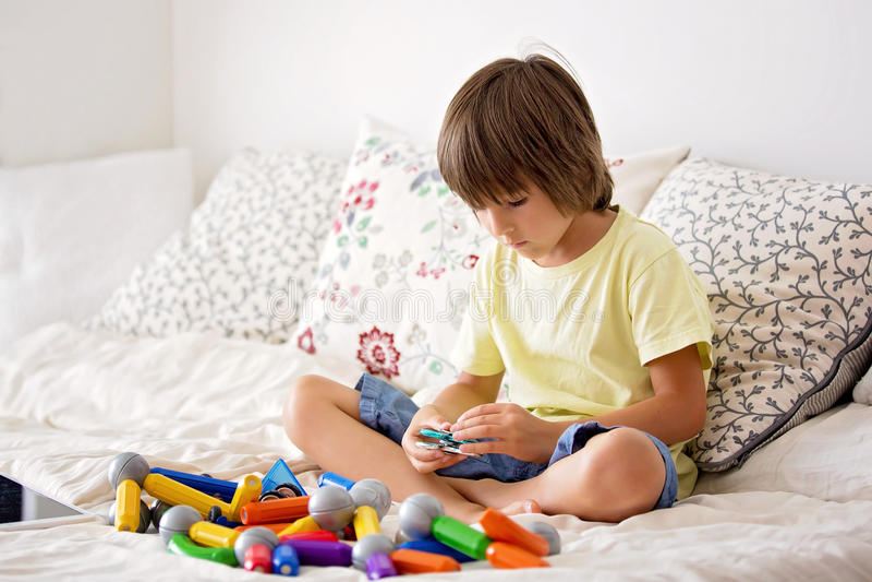 与坐立不安锭床工人应力消除玩具的年轻男孩戏剧 免版税库存照片