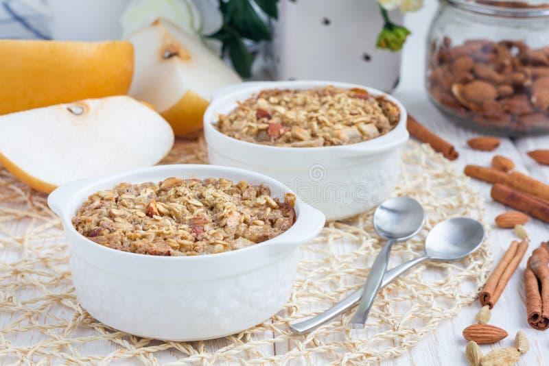 与坚果、杏仁牛奶、香料和亚洲梨的被烘烤的燕麦粥 免版税库存图片