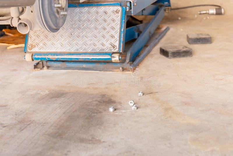 与坚果和车轮钳位机器的车库地板在新的轮胎替换的过程中 免版税库存图片