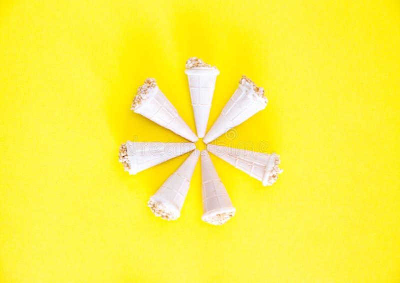 与坚果的冰淇淋在奶蛋烘饼杯子 以在黄色背景,薄酥饼垫铁被安排,特写镜头的一朵花的形式 免版税库存照片