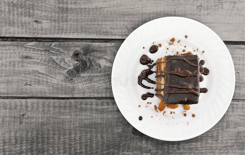 与坚果的巧克力蛋糕切片在木桌上的板材,顶视图 免版税库存图片