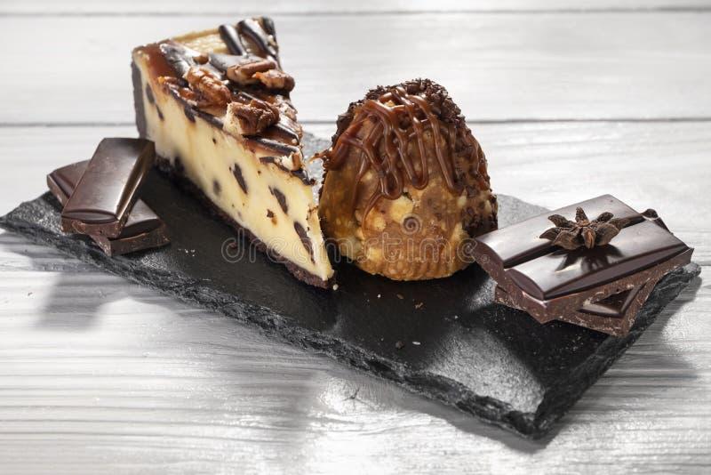 与坚果的果仁巧克力乳酪蛋糕,巧克力,在石板材的甜蛋糕在白色木背景 免版税库存照片