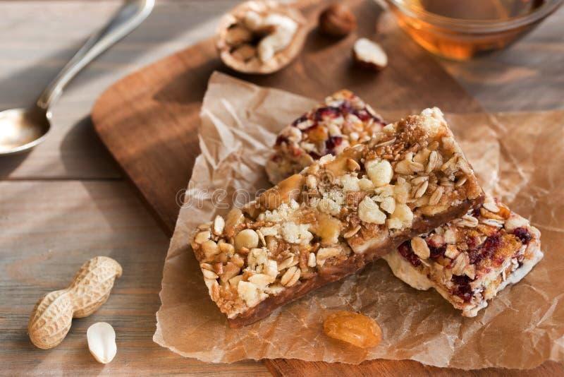 与坚果的格兰诺拉麦片棒和干果子和蜂蜜在木背景快餐健康活的 免版税库存图片