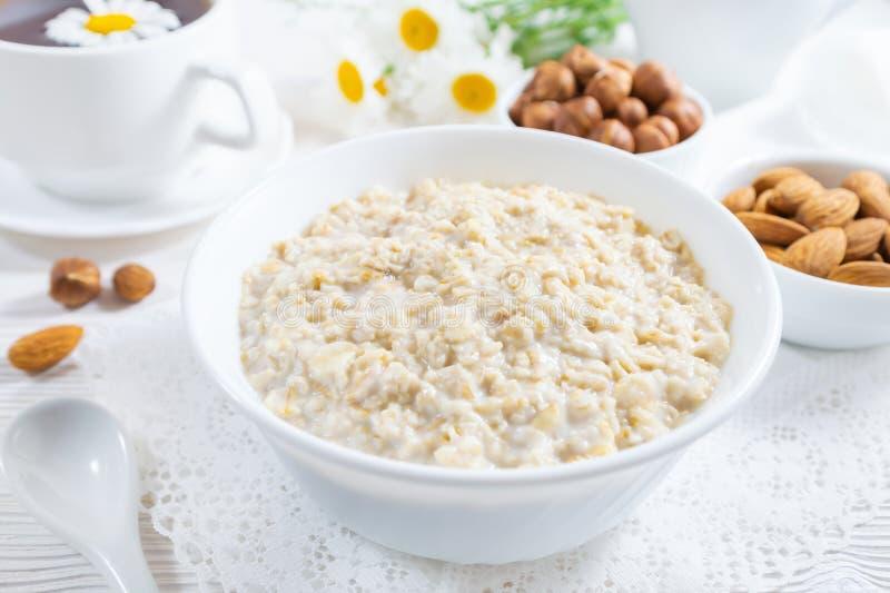 与坚果的燕麦粥在白色木桌上的碗 免版税图库摄影