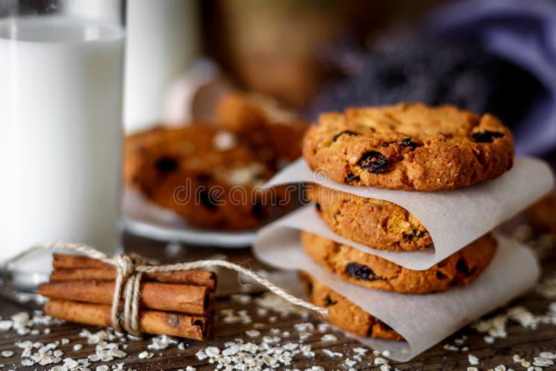 与坚果的自创麦甜饼和葡萄干和杯在黑暗的木背景,特写镜头,选择聚焦的牛奶 免版税库存图片