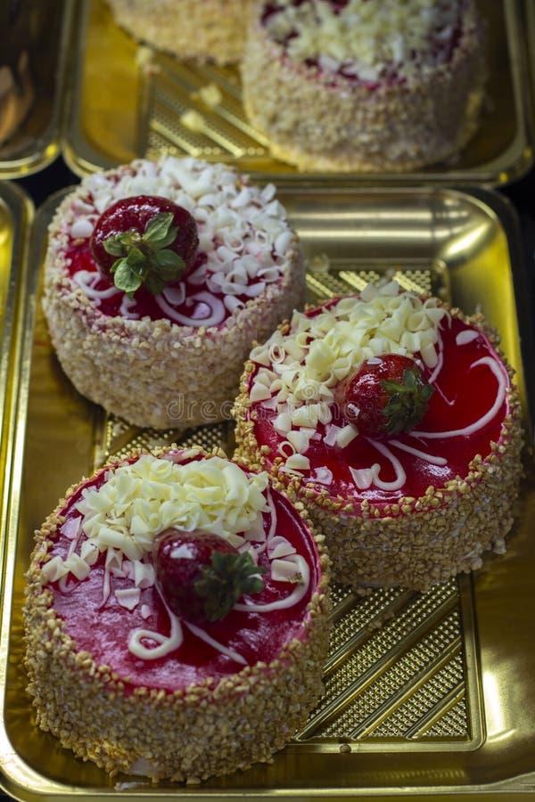 与坚果面包屑、新鲜的草莓在果冻和巧克力片的松糕草莓微型蛋糕 图库摄影