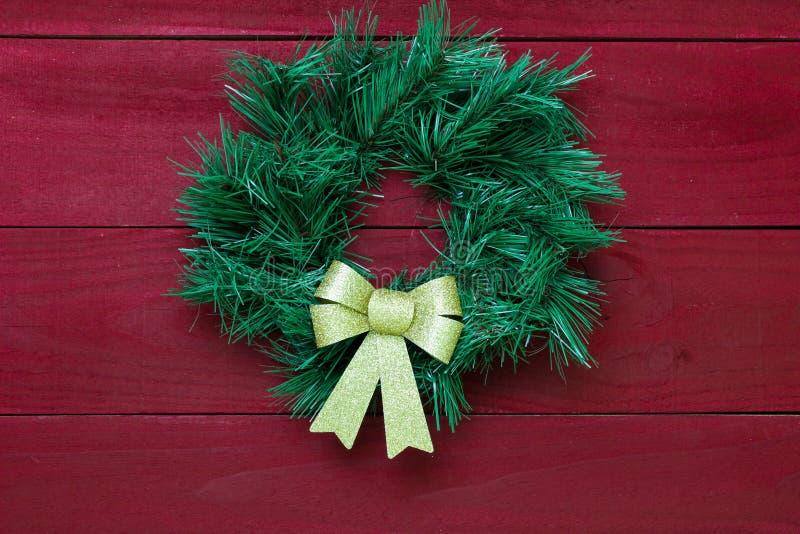 与垂悬在古色古香的红色木门的金弓的绿色圣诞节花圈 免版税图库摄影