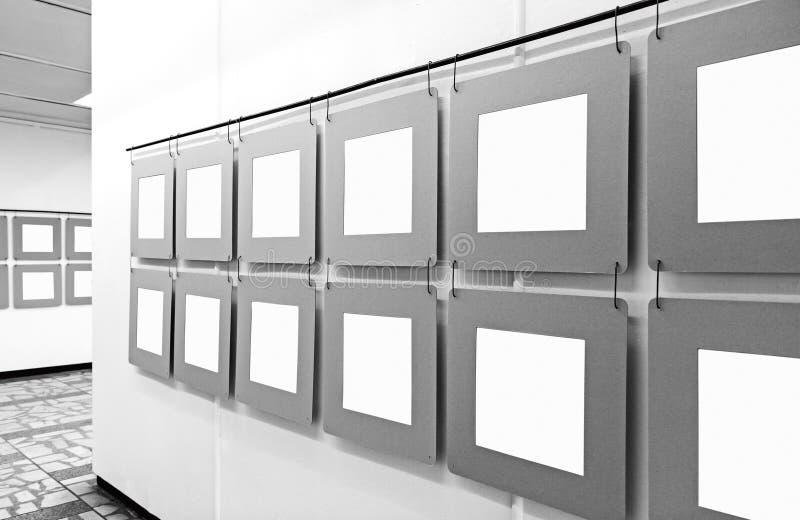 与垂悬在墙壁上的白纸海报的美术馆大模型 库存照片