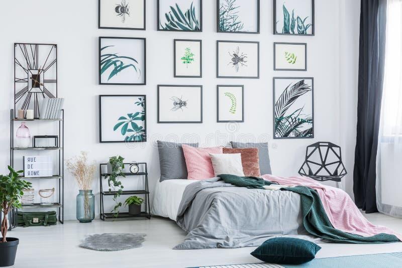 与垂悬在明亮的卧室内部的墙壁上的简单的海报的画廊与在床、新鲜的植物和塑料柴上的许多枕头 免版税图库摄影