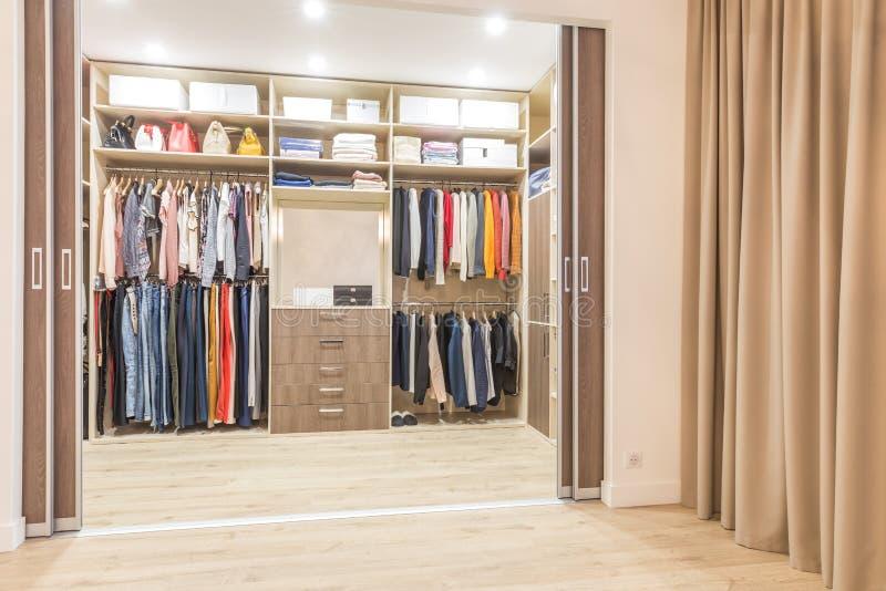 与垂悬在步行的路轨的衣裳的现代木衣橱在壁橱 免版税库存图片