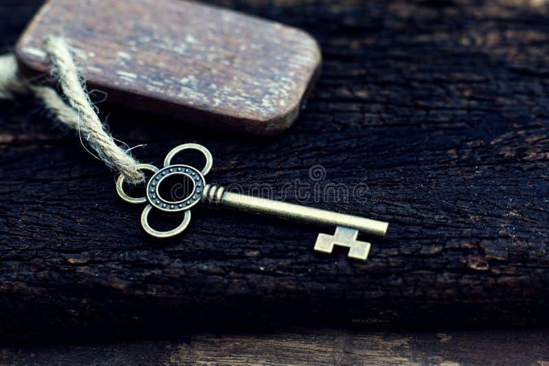与垂悬在老木板条的木家庭钥匙圈的葡萄酒钥匙有迷离绿色庭院背景 库存照片