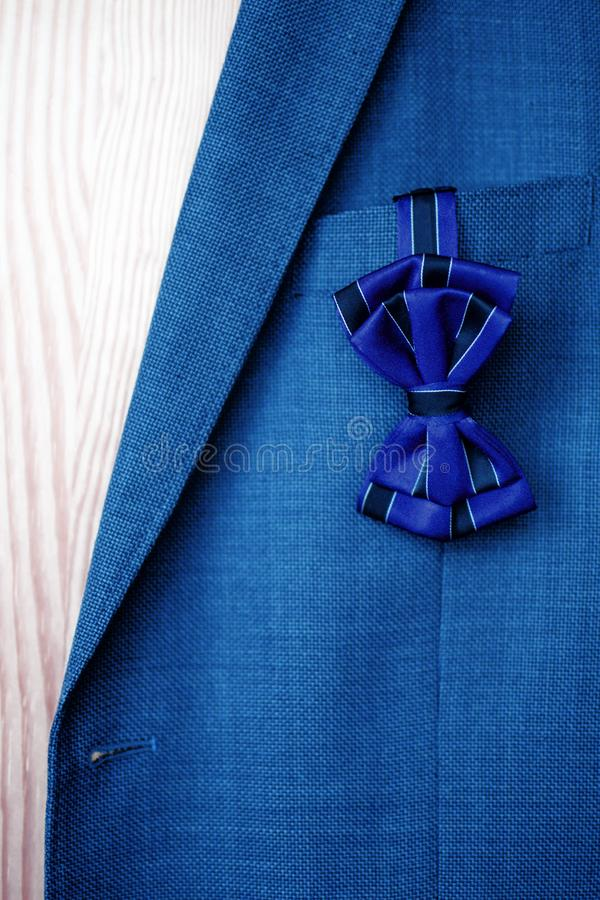 与垂悬在蓝色衣服夹克` s口袋外面的黑条纹的深蓝蝶形领结 图库摄影