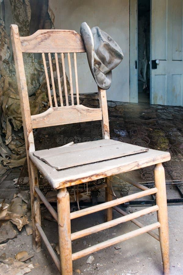 与垂悬岗位的帽子的老被放弃的椅子在Bodie状态历史公园在加利福尼亚,一个古金色仓促采矿镇 免版税库存照片