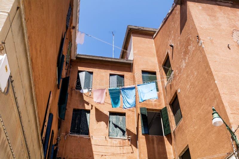 与垂悬的洗衣店的典型的意大利橙色大厦 图库摄影