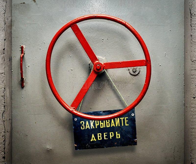 与垂悬破旧的牌的装甲的地堡门与俄国人关闭门警告 免版税库存图片